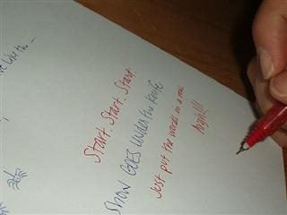 person writing on piece of paper with red ink
