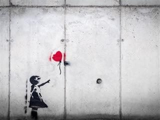 banksy or banksy  knockoff. wheatpaste grafitti art of girl on wall reaching up for a  red heart-shaped balloon