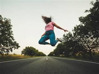 woman leaping in middle of the road