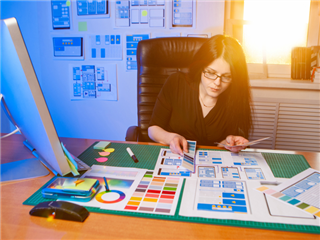 A mobile app designer works on a project in her office on a sunny morning - prototyping realism concept