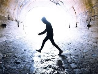 person walking through a tunnel with water flowing through it