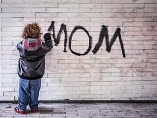 boy writing 'mom' on a wall