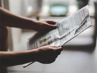 Close up of hands holding a newspaper.