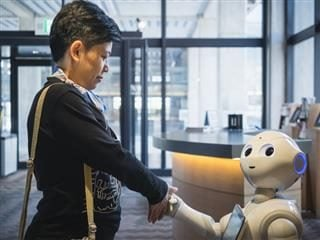 Robot welcoming businesswoman into the office