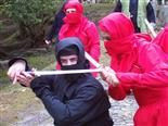 People dressed up like ninjas holding swords.