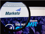 Photo of Marketo homepage on a monitor screen through a magnifying glass.