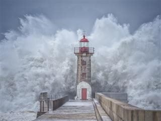 A big wave crashing over a secure lighthouse - security lookout concept