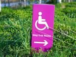 "sign set in the grass pointing to wheelchair accessible route. reads ""step free route"""