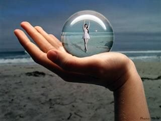 Person holding a globe of a tiny dancer