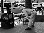 man leans over with hands on knees looking into a newspaper box.
