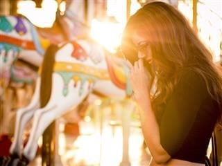 woman by a carousel in sunlight