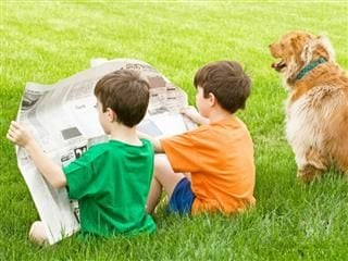 Two boys sitting in grass reading a newspaper next to a dog sitting in grass. The dog is not reading a newspaper.