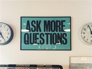 """Sign reading, """"Ask more questions"""""""