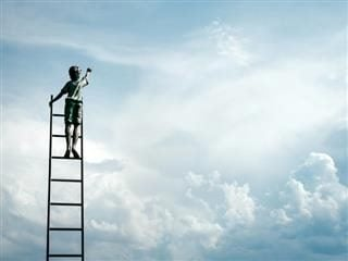 boy standing on ladder reaching for clouds