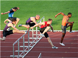 group of men clearing hurdles on a race track