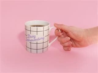 hand holding a white coffee mug with the message Busy Introverting against a pink background
