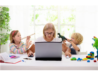 a woman flanked by two kids raising toys to her ear as she tries to work on a laptop.