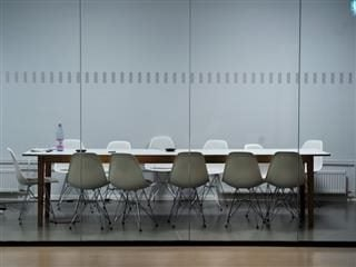 an empty meeting room with table and chairs
