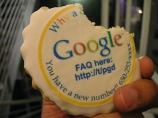 "A person holds a frosted cookie with the words ""Google FAQ here; you have a new number"" other words are cut off because a piece of the cookie is missing"