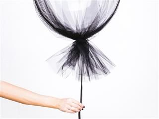 woman's hand holding a black mesh balloon
