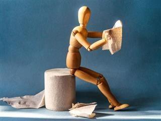 A wooden statue of a sitting man reading a newspaper - Newsbyte Concept