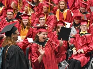 Graduates in red cap and gowns celebrating.