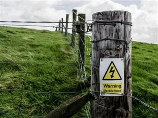 warning: electric fence sign on a post in the middle of a green field