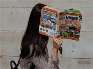 woman hiding her face behind a book