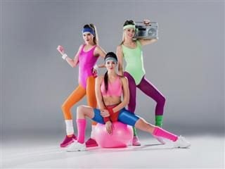 three women dressed in '80s exercise outfits