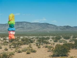 "a sculpture in the desert, a stack of colorful rocks, ""seven magic mountains"""