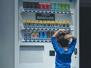 child standing in front of vending  machine looking at all of the choices