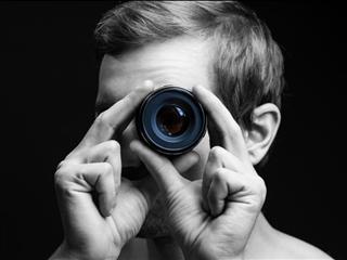 A man looking through a camera lens -  Marketing Microinteraction concept