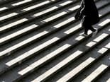 a person walking up sunlit steps
