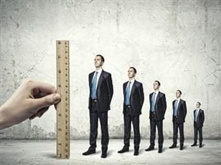 Employers hand measuring potential skills of employees standing in line with a ruler