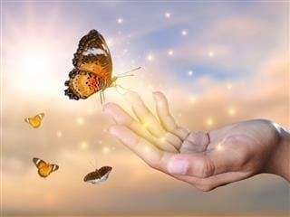 stock photo of a hand, butterflies, stars, who knows what else is going on here?