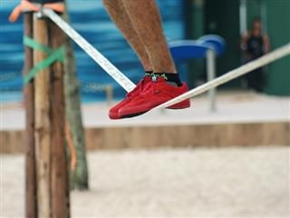 close up of a man who is balancing on a tightrope's red sneakers