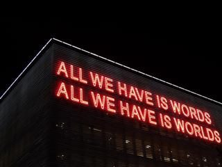 "Neon sign at top of building reading ""All we have is words//All we have is worlds"""
