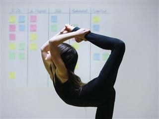A gymnast in a difficult pose with an agile project board background