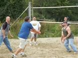 Men play volleyball in a company outing.
