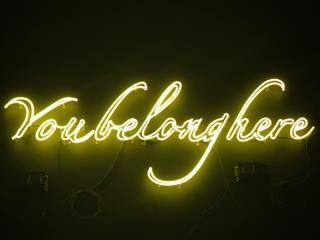 yellow neon sign with the message you belong here