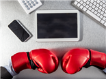 Boxing gloves facing technology screens, digital tablet, calculator and computer on an office desk - project management tool showdown