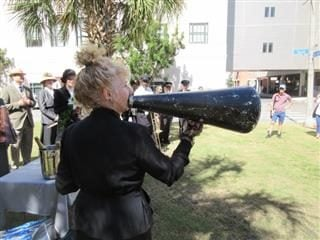a woman talking on a megaphone outside