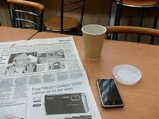 Newspaper, coffee and iPhone on a table.