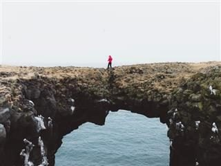 person in red parka walking over natural bridge over water