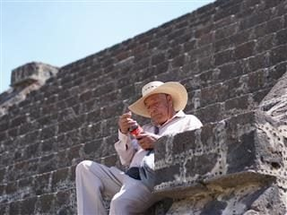 man examining a coca cola bottle in San Juan Teotihuacán, Mexico