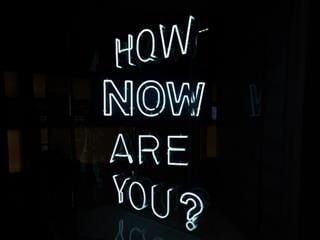 """neon sign reading: """"How Now Are You?"""""""