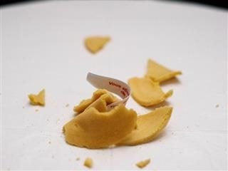 fortune cookie, broken on a table, fortune sticking out