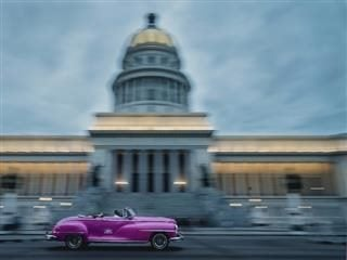 someone driving a hot pink vintage car past a municipal building
