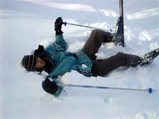 skier lays down in pile of snow