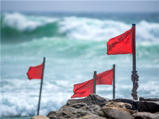 Red warning flags on a rocky  beach